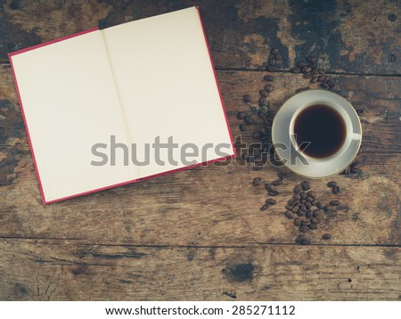 Overhead shot of coffee concept with empty cup, tea towel and an open book with blank pages