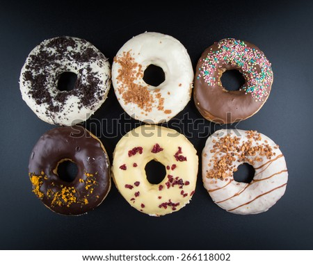 overhead shot of color doughnuts on black table - stock photo