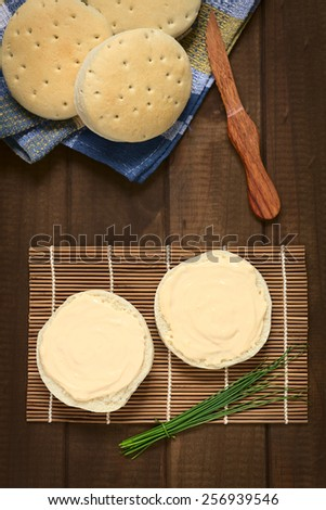 Overhead shot of cream cheese spread on bun with a bundle of chives on the side, photographed with natural light  - stock photo