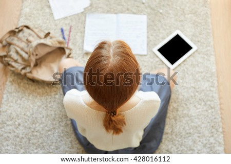 Overhead shot of female freelancer working on her project while sitting on the floor using digital tablet and making notes in copybook. Redhead student girl doing homework at home. Selective focus - stock photo