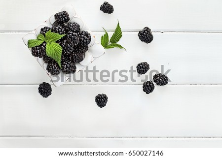 Overhead shot of fresh blackberry fruit over white wood table top. Room for copy space.