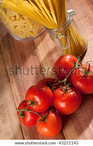 Overhead shot of fresh tomatoes next to a glass container with raw pasta - stock photo