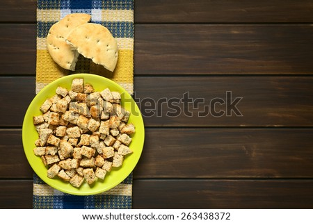 Overhead shot of freshly toasted homemade croutons made of wholegrain bread, photographed on dark wood with natural light - stock photo
