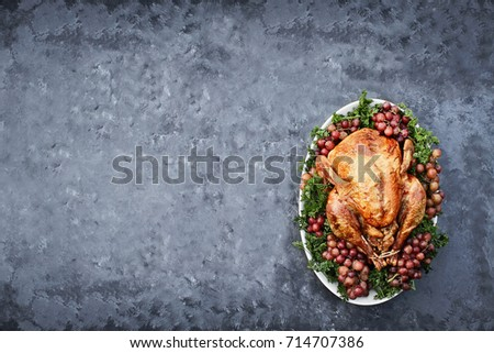 Overhead shot of golden roasted Thanksgiving turkey  on a platter garnished with parsley and fresh grapes against a rustic background. Photo shot in flat lay style.