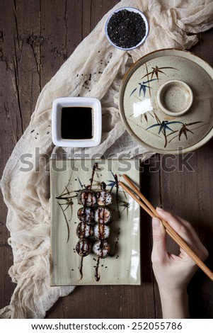 overhead shot of hands with chopstick taking hosomaki sushi from plate - stock photo