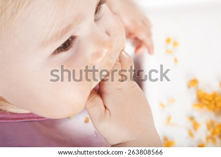 overhead shot of one year age caucasian baby pink plastic bib eating meal yellow orange rice paella with her hand in white high-chair
