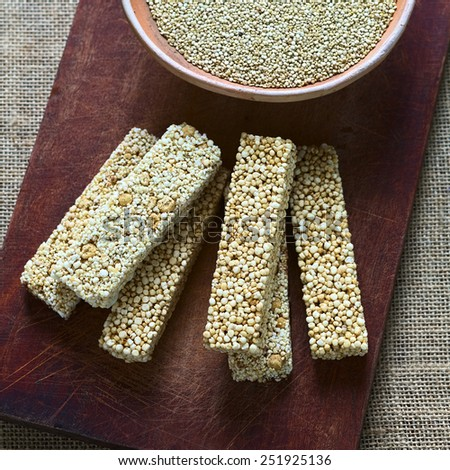 Overhead shot of quinoa cereal bars, one with honey the other with amaranth, bowl of raw white quinoa on wooden board photographed with natural light (Selective Focus, Focus on the upper cereal bars) - stock photo