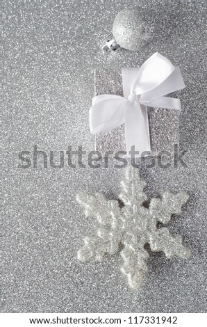 Overhead shot of three silver glittering Christmas ornaments on silver glitter background. Includes a bauble, a Christmas gift with white ribbon bow, and a star shaped snowflake.  Copy space to left.