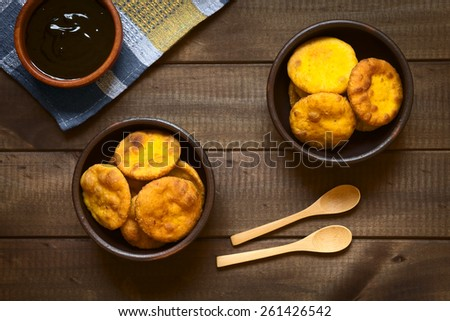 Overhead shot of traditional Chilean Sopaipilla fried pastry made with mashed pumpkin in the dough, served with Chancaca sweet sauce, photographed on dark wood with natural light - stock photo