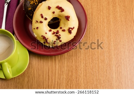 overhead shot of two doughnuts on a marsala plate and coffee - stock photo