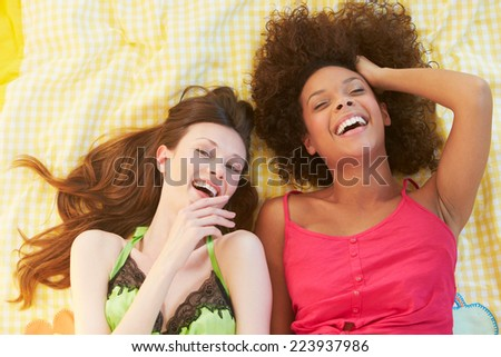 Overhead Shot Of Two Female Friends Lying On Bed