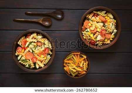 Overhead shot of two rustic bowls of pasta salad made of tricolor fusilli, sweet corn, cucumber, cherry tomato and sausage, photographed on dark wood with natural light - stock photo
