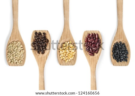 Overhead shot of variety of pulses with coffee beans on wooden spatula. - stock photo