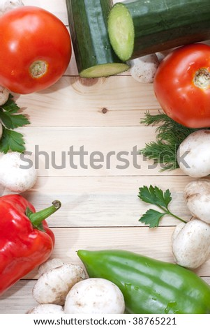 Overhead shot of veggies with empty space of wooden background inthe middle - stock photo