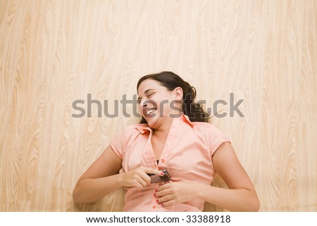 overhead shot of woman lying on back using mobile device