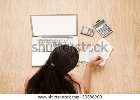 overhead shot of woman sitting on floor with laptop - stock photo