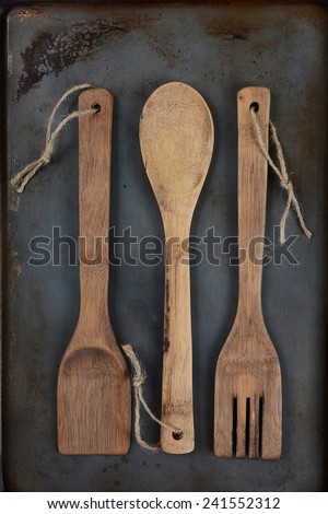 Overhead shot of wooden kitchen utensils, fork, spoon, and spatula, with twine through the handle hole on a used metal baking sheet. Vertical Format with middle spoon inverted.. - stock photo