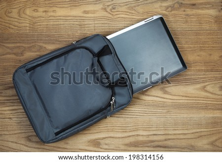 Overhead tilted view of laptop computer and carry case, on rustic wooden boards - stock photo