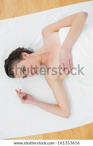Overhead view of a beautiful young woman lying on towel in beauty salon