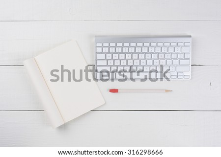 Overhead view of a blank note pad and a computer keyboard on a white wood table. Business desk mock up. - stock photo