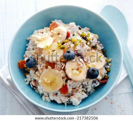 Overhead view of a bowl of breakfast cereal topped with fresh and dried fruit and chopped pistachio nuts - stock photo