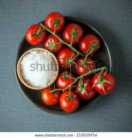 Overhead view of a bunch of ripe red cherry tomatoes on the vine and a bowl of coarse natural sea salt for cooking ingredients on a grey cloth background in square format - stock photo