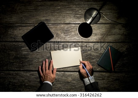 Overhead view of a businessman working late at his desk by the light of a desk lamp about to write on a blank card with his pen, tablet computer alongside with blank screen. - stock photo