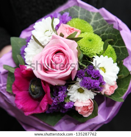 Overhead view of a colourful bouquet of mixed flowers arranged in purple tissue paper to be carried as an accessory at a wedding or celebration