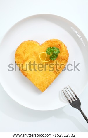 Overhead view of a crispy golden heart shaped escalope of veal pan fried in breadcrumbs garnished with fresh parsley and served on a plate - stock photo