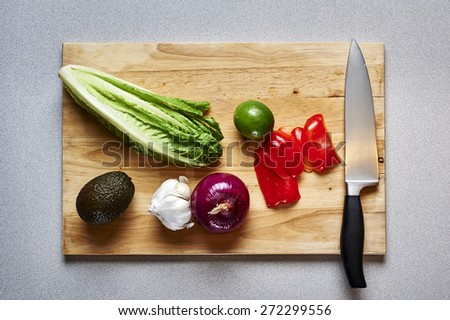 overhead view of a cutting board with vegetables and a knife - stock photo