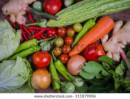 Overhead view of a delicious assortment of farm fresh vegetables, herbs and mushrooms spread out on a rustic wooden table,rustic style