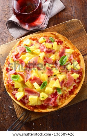 Overhead view of a delicious freshly baked ham and pineapple pizza on a thin crispy crust standing on an old wooden board on a kitchen table. More pizza at my port. - stock photo
