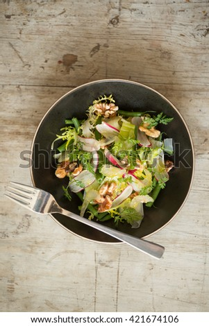 Overhead view of a dining fork on bowl of light vegetable salad on a wooden surface - stock photo