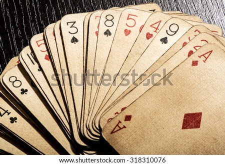 Overhead view of a fanned deck of old grungy discolored dirty vintage playing cards, conceptual of gambling and casinos - stock photo