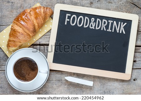Overhead view of a fresh cup of coffee and a flaky croissant on an old school slate over a rustic wooden background.With text Food and Drink on blackboard - stock photo