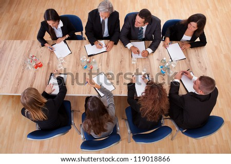Overhead view of a group of professional business people in a meeting seated around a wooden table with their notepads - stock photo