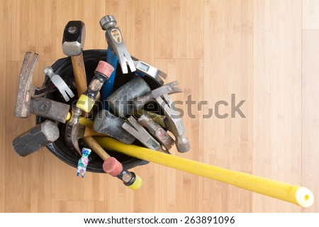 Overhead view of a large selection of different types of hammers for every occasion standing in a bucket on a wooden background with copy space - stock photo