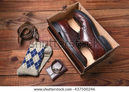 Overhead view of a pair of men's shoes in a shoebox. Socks, belt, watch and wallet lie on the floor next to the box.