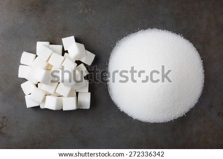 Overhead view of a pile of granulated white sugar and a mound of sugar cubes, on a used baking sheet. - stock photo