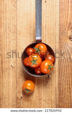 Overhead view of a retro saucepan full of fresh ripe red whole tomatoes on a wooden tabletop with woodgrain and copyspace - stock photo