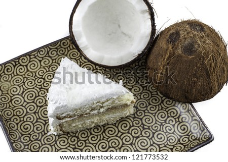 Overhead view of a slice of coconut cake on a plate with a crack coconut next to it. - stock photo
