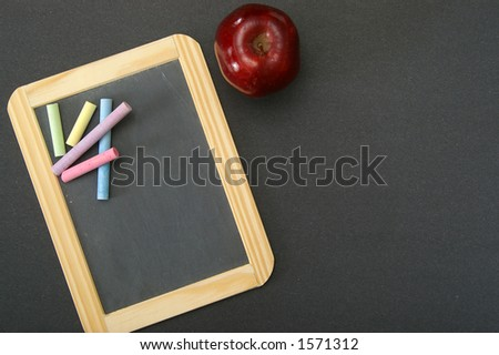 Overhead view of a teacher's desk, with chalkboard and apple. Plenty of area for your own text. - stock photo