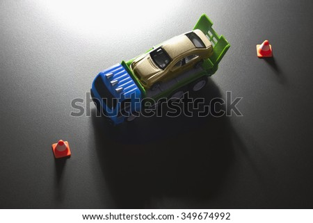 Overhead view of a toy car on a pick up truck between road traffic cones. - stock photo
