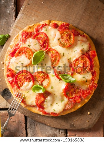 Overhead view of a whole uncut scrumptious fresh cheese and tomato pizza on a wooden board - stock photo
