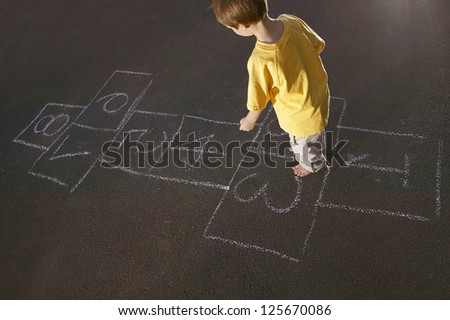 Overhead view of a young boy in a yellow shirt playing hopscotch marked out on an apshalt surface - stock photo