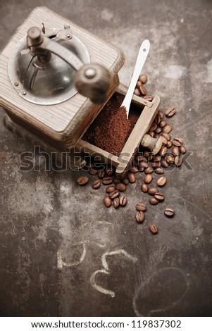 Overhead view of an old manual wooden coffee grinder with an open drawer filled with freshly ground coffee surrounded by scattered coffee beans on a grungy chalkboard with copyspace - stock photo