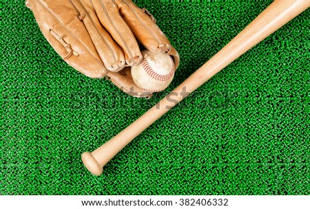 Overhead view of baseball mitt, ball and bat on artificial grass
