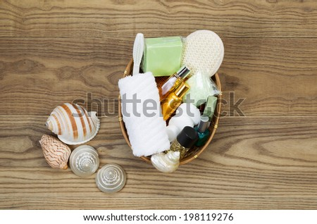 Overhead view of bath and shower accessories placed in basket on rustic wooden boards. Items include hand towel, scrub brush, lotion, soap, soaking salts, perfume, and sea shells.   - stock photo