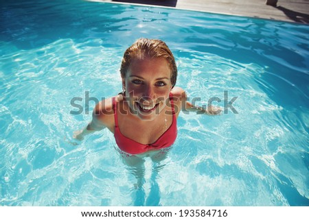 Overhead view of beautiful young lady wearing red swimwear standing in a pool looking at camera. Pretty young woman relaxing in a swimming pool.