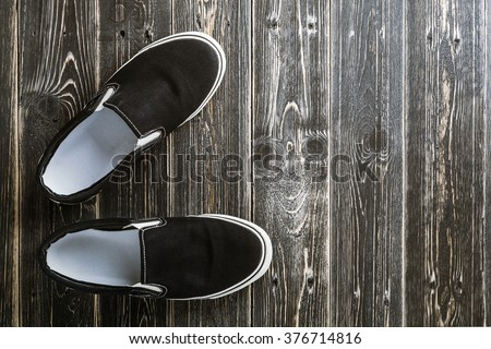 Overhead view of black slip on shoes on rustic wood board